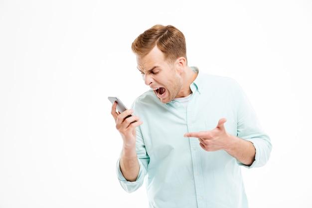 Jovem empresário irritado falando e gritando no celular na parede branca