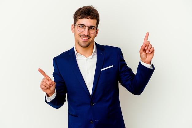Jovem empresário isolado na parede branca apontando para diferentes espaços de cópia, escolhendo um deles, mostrando com o dedo