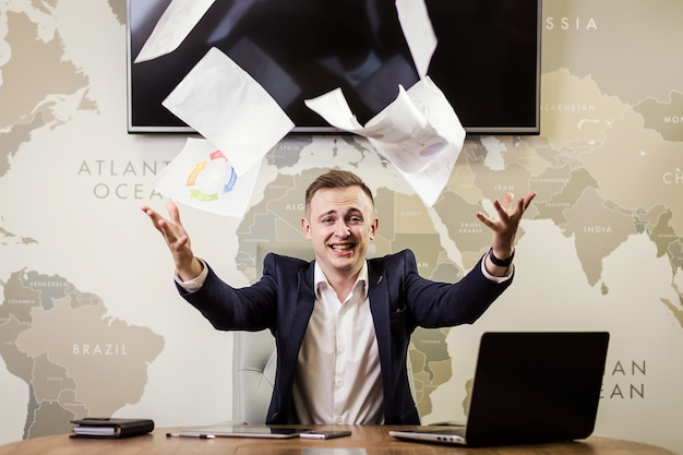 Jovem empresário jogando algumas folhas de papel no ar, negócios, pessoas, estresse, emoções e falhar conceito - empresário irritado jogando papéis no escritório