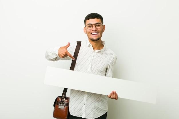 Jovem empresário latino-americano, segurando um cartaz
