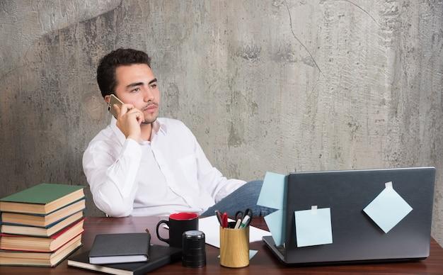 Jovem empresário ligando para alguém na mesa do escritório.