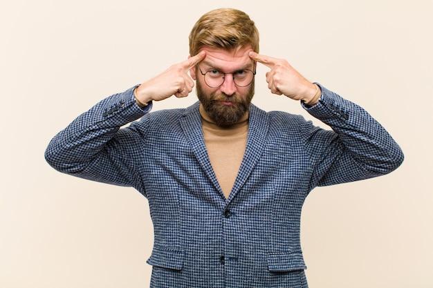 Jovem empresário loiro com um olhar sério e concentrado, de brainstorming e pensando em um problema desafiador