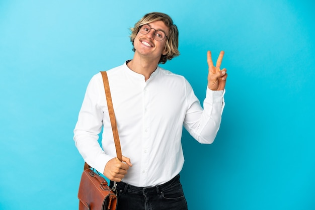 Jovem empresário loiro isolado em azul mostrando sinal de vitória com as duas mãos