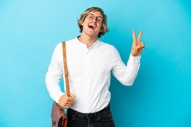 Jovem empresário loiro isolado em um azul sorrindo e mostrando sinal de vitória