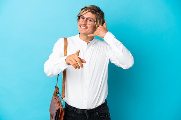 Jovem empresário loiro isolado na parede azul fazendo gestos de telefone e apontando para a frente