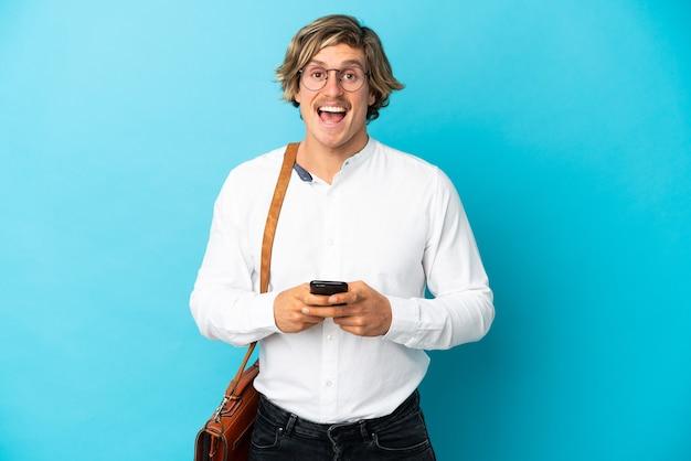 Jovem empresário loiro isolado na parede azul surpreso e mandando uma mensagem