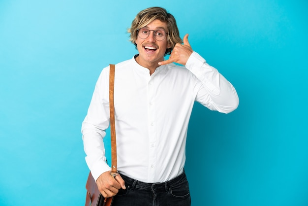 Jovem empresário loiro isolado no azul fazendo gesto de telefone