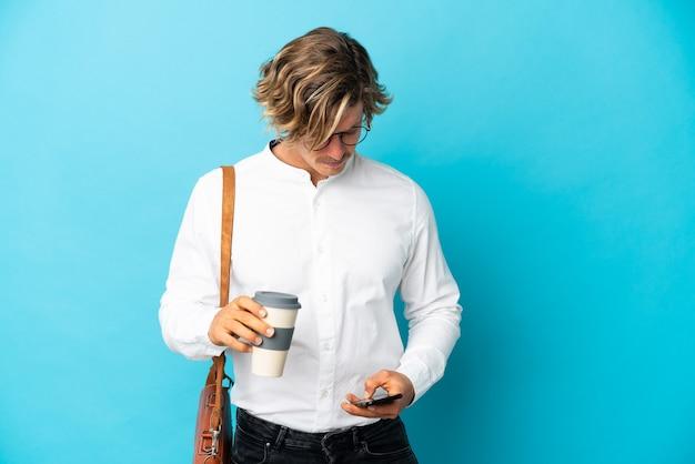 Jovem empresário loiro isolado no azul segurando um café para levar e um celular