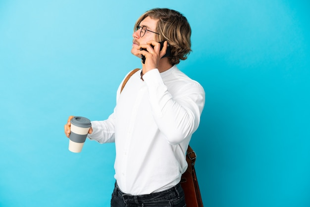 Jovem empresário loiro isolado segurando um café para levar e um celular