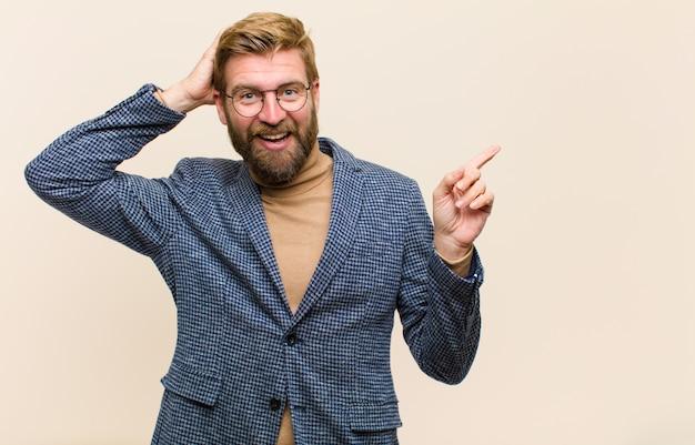 Jovem empresário loiro rindo, parecendo feliz, positivo e surpreso, percebendo uma ótima idéia apontando para o espaço lateral da cópia