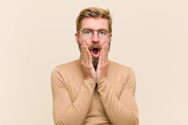 Jovem empresário loiro, sentindo-se chocado e assustado, olhando aterrorizado com a boca aberta e as mãos nas bochechas