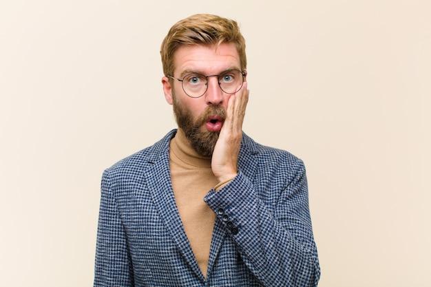 Jovem empresário loiro, sentindo-se chocado e atônito, segurando frente a frente em descrença com a boca aberta