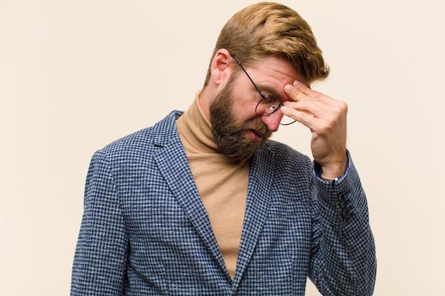 Jovem empresário loiro, sentindo-se estressado e frustrado, tocando a testa e sofrendo de enxaqueca com fortes dores de cabeça
