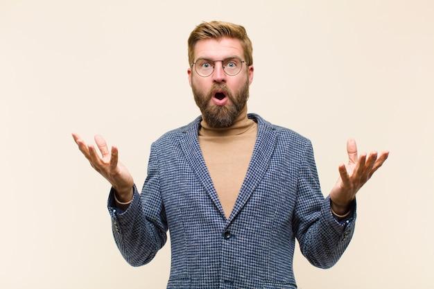 Jovem empresário loiro, sentindo-se extremamente chocado e surpreso, ansioso e em pânico, com um olhar estressado e horrorizado