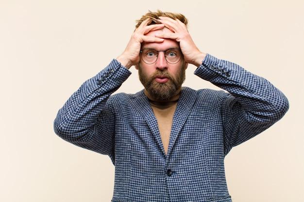 Jovem empresário loiro, sentindo-se horrorizado e chocado, levantando as mãos na cabeça e entrando em pânico por um erro