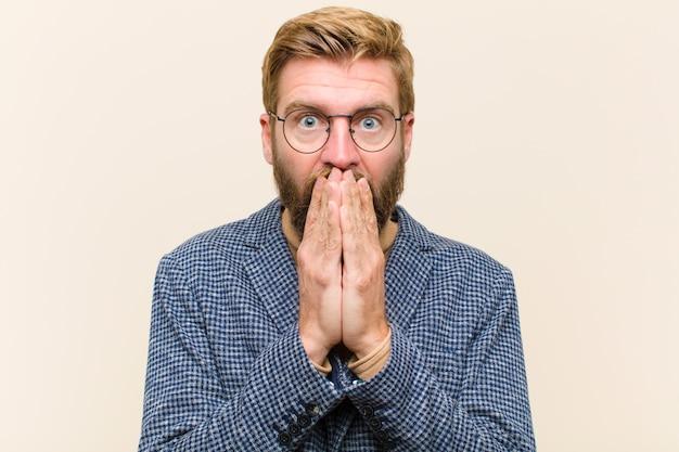 Jovem empresário loiro, sentindo-se preocupado, chateado e assustado, cobrindo a boca com as mãos, parecendo ansioso e tendo estragado