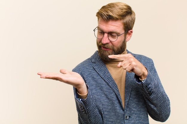 Jovem empresário loiro sorrindo alegremente e apontando para copiar o espaço na palma da mão, mostrando ou anunciando um objeto