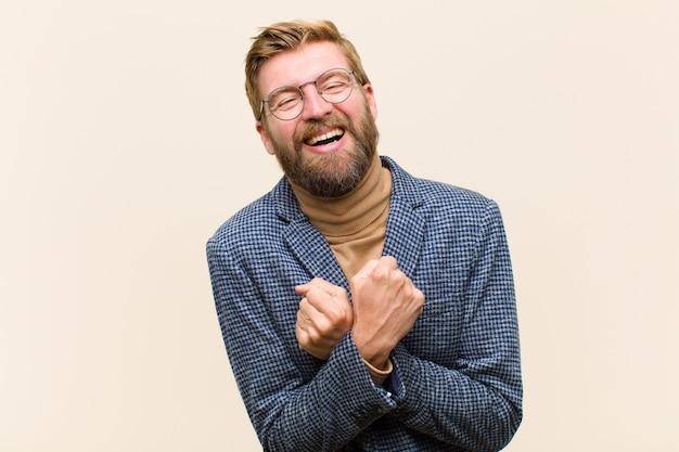 Jovem empresário loiro sorrindo alegremente e comemorando, com os punhos cerrados e braços cruzados, sentindo-se feliz e positivo