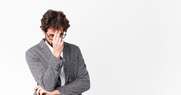 Jovem empresário louco sentindo estressado, infeliz e frustrado, tocando a testa e sofrendo de enxaqueca de forte dor de cabeça contra a parede