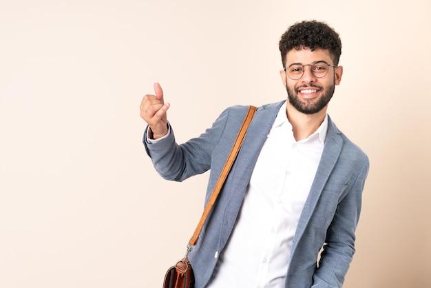 Jovem empresário marroquino isolado na parede bege fazendo gesto de guitarra