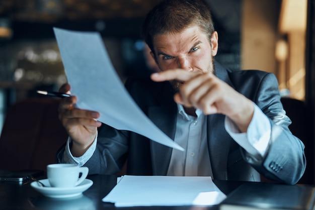 Jovem empresário masculino se senta em uma mesa com papéis e bebe café, olha pela janela