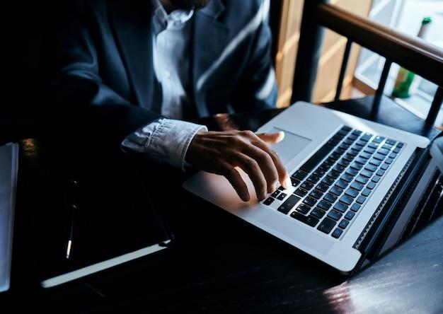 Jovem empresário masculino se senta em uma mesa com papéis e bebe café