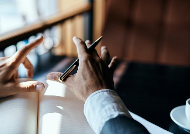Jovem empresário masculino se senta em uma mesa com papéis
