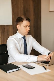 Jovem empresário masculino trabalhando no laptop no escritório.