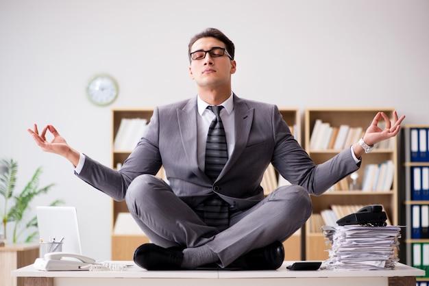 Jovem empresário meditando no escritório