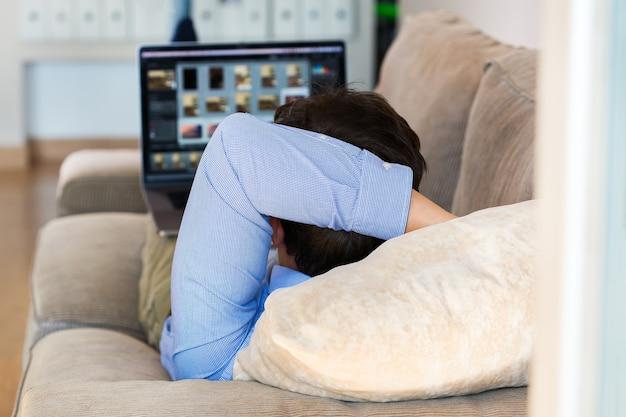 Jovem empresário milenar, freelancer, trabalhando em um laptop deitado no sofá. composição do estilo de vida com luz natural. conceito de ficar em casa