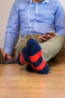 Jovem empresário milenar, freelancer, trabalhando em um laptop sentado no chão. composição do estilo de vida com luz natural. conceito de ficar em casa