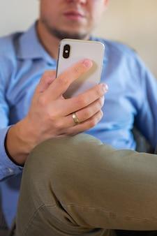 Jovem empresário milenar, freelancer, trabalhando em um telefone, sentado no sofá. composição do estilo de vida com luz natural. conceito de ficar em casa