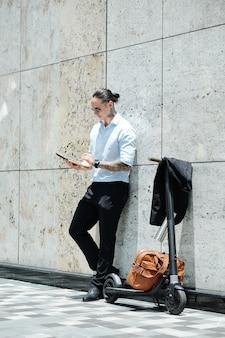Jovem empresário moderno em pé ao ar livre ao lado de sua scooter e lendo documento no tablet digital