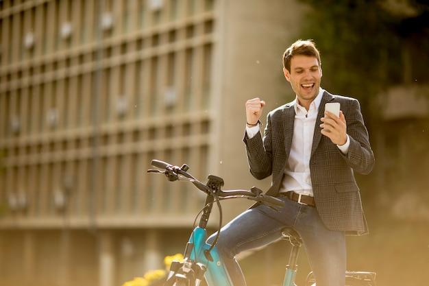 Jovem empresário na ebike recebeu notícias do gret pelo celular