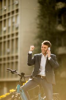 Jovem empresário na ebike usando telefone celular