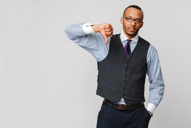 Jovem empresário negro com uma expressão de antipatia séria e dissidente com os polegares para baixo em desaprovação.