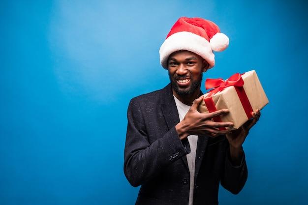 Jovem empresário negro com uma expressão feliz segurando um presente de natal