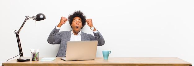 Jovem empresário negro comemorando um sucesso inacreditável como um vencedor que parece animado e feliz dizendo, pegue isso!