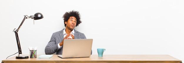 Jovem empresário negro planejando e conspirando, pensando em truques e fraudes tortuosos, astúcia e traição em uma mesa