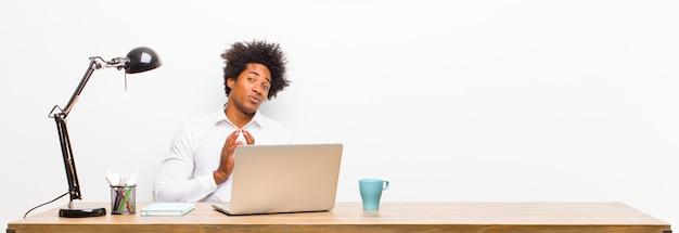 Jovem empresário negro se sentindo orgulhoso, travesso e arrogante enquanto trama um plano maligno ou pensa em um truque em uma mesa