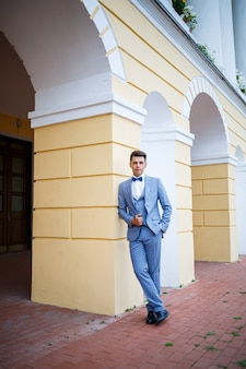 Jovem empresário noivo no dia do casamento, roupas elegantes, um passeio no parque