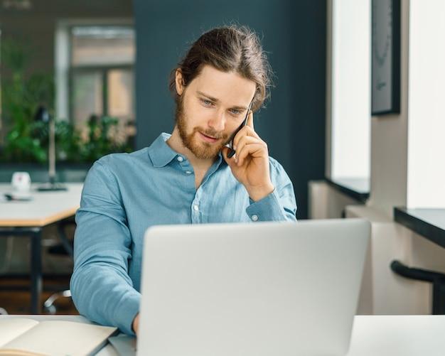 Jovem empresário ocupado falando no celular no escritório