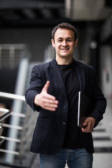 Jovem empresário, oferecendo o aperto de mão segurando laptop recebê-lo no escritório