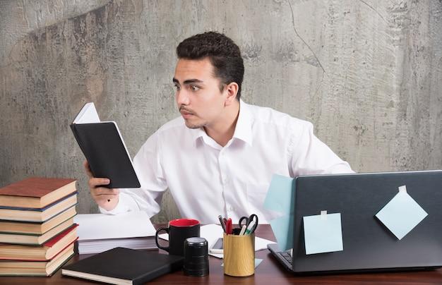 Jovem empresário, olhando de perto para o caderno na mesa.