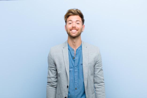 Jovem empresário, olhando feliz e pateta, com um sorriso largo, divertido e maluco e olhos bem abertos em azul