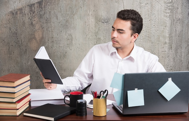 Jovem empresário olhando intensamente para o caderno na mesa.