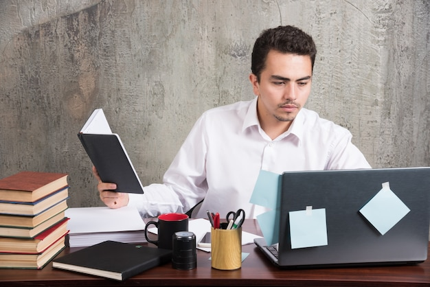 Jovem empresário olhando o laptop na mesa do escritório.