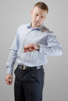 Jovem empresário olhando para a hora do relógio de pulso. isolado na superfície branca.