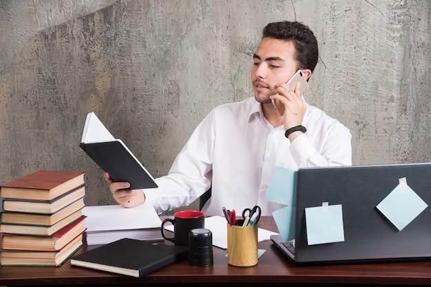 Jovem empresário olhando para o caderno e falando na mesa do escritório.