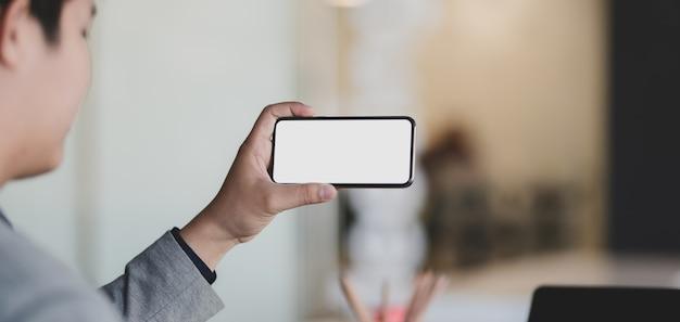 Jovem empresário, olhando para o smartphone de tela em branco